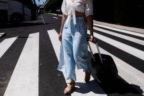 Primer plano de una joven con equipaje cruzando una calle en el aeropuerto - foto de stock