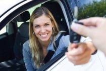 Porträt der lächelnde junge Frau Blick in die Kamera halten Auto Schlüssel und geben Sie es an jemand durchs Fenster — Stockfoto