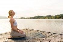 Молодая женщина практикует йогу на причале у озера — стоковое фото