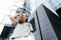 Porträt einer lächelnden Frau, die in die Kamera blickt, moderne Bürogebäude im Hintergrund, Blick in den Tiefflug — Stockfoto