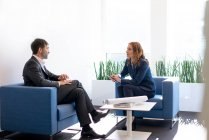 Безробітна жінка і бізнесмен, які сидять у кріслах при офісі, розмовляє — стокове фото