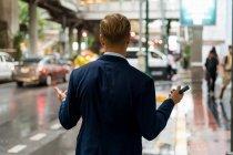 Молодой бизнесмен держит смартфон в Бангкоке в дождливый день — стоковое фото
