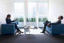 Сміється бізнес і бізнесмен сидячи в офісній кімнаті — стокове фото
