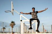 Портрет молодого человека, сидящего на футбольном вороте против неба — стоковое фото