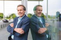 Portrait of confident senior businessman standing at glass front — Stock Photo