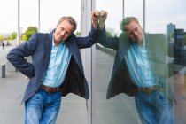 Portrait of confident senior businessman leaning against glass front — Stock Photo