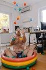 Божевільний бізнесмен, який сидить у басейні в офісі граючи з м'ячами. — стокове фото