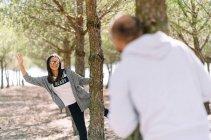 Усміхнена жінка в окулярах на дереві, піднімаючи руку. — стокове фото
