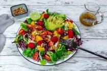 Placa de colorida ensalada mixta con queso feta, remolacha común, nueces, piñones, frambuesas, naranjas y ensalada de maíz - foto de stock