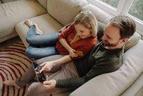 Пара сидить вдома на дивані, користуючись цифровим планшетом. — стокове фото