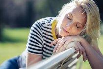 Blond lächelnde Frau sitzt auf einer Bank und blickt in die Kamera — Stockfoto
