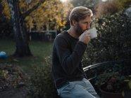 Man having a coffee break in garden — Stock Photo