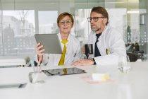 Dos doctores sentados en el escritorio usando tableta - foto de stock