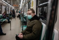 Jeune homme en train de banlieue, portant un masque facial, utilisant un smartphone — Photo de stock