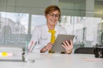 Médico sentado en el escritorio usando tableta - foto de stock