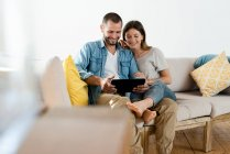 Щаслива пара у сучасній вітальні сидить на дивані і разом дивиться на табличку. — стокове фото