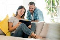 Щаслива пара вдома, у сучасній вітальні на дивані, дивиться на табличку разом. — стокове фото