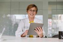 Retrato del médico sonriente sentado en el escritorio usando tableta - foto de stock