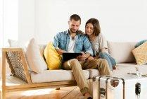 Усміхнена пара вдома, у сучасній вітальні, сидить на дивані і разом дивиться на табличку. — стокове фото