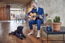 Старший бізнесмен сидить в офісі, граючи на гітарі для свого собаку. — стокове фото