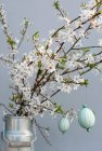 Blossoming blackthorn branches decorated with yarn wrapped Easter eggs — Stock Photo