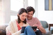 Пара, яка сиділа вдома на дивані з планшетом. — стокове фото