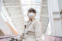 Жінка з масками обличчя та одноразовими рукавицями на ескалаторі в торговому центрі. — стокове фото