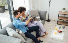 Щаслива пара користується цифровою табличкою, сидячи на дивані в пентхаусі. — стокове фото