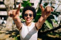 Зблизька усміхнена жінка у сонцезахисних окулярах з піднятими руками на відкритому повітрі. — стокове фото