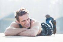 Улыбающийся красивый мужчина среднего возраста смотрит в сторону, лежа на тропинке в солнечный день — стоковое фото