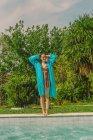 Посміхнена жінка у блакитному плащі стоїть біля басейну. — стокове фото