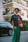 Портрет усмішки молодої жінки з захисною маскою, що стоїть на вулиці — стокове фото