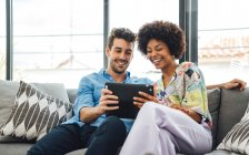 Щаслива багатоетнічна пара використовує цифрову табличку, сидячи на дивані в пентхаусі. — стокове фото