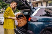 Портрет усміхненої жінки з захисною маскою, що кладе кошик у багажник свого автомобіля. — стокове фото