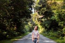 Духовний молодий чоловік, стоячи на дорозі серед дерев у лісі, дивиться вгору. — стокове фото