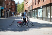 Young man crossing the street with  rental bike, London, UK — Foto stock