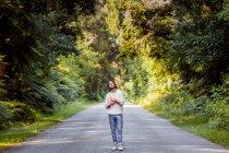 Молодий чоловік дивиться вгору, тримаючи книжку на сільській дорозі серед дерев у лісі. — стокове фото