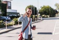 Giovane sorridente che parla sul cellulare mentre attraversa la strada in città — Foto stock