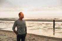 Вдумчивый человек с руками в карманах, стоящими у моря на закате — стоковое фото