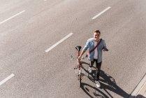 Uomo sorridente con bicicletta attraversando strada in città nella giornata di sole — Foto stock