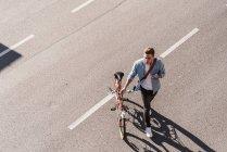 Giovane che attraversa la strada con la bicicletta in città — Foto stock