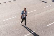Uomo che utilizza il telefono cellulare mentre attraversa la strada in città — Foto stock