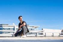 Красивый мужчина смотрит в сторону, приседая на крыше в солнечный день — стоковое фото