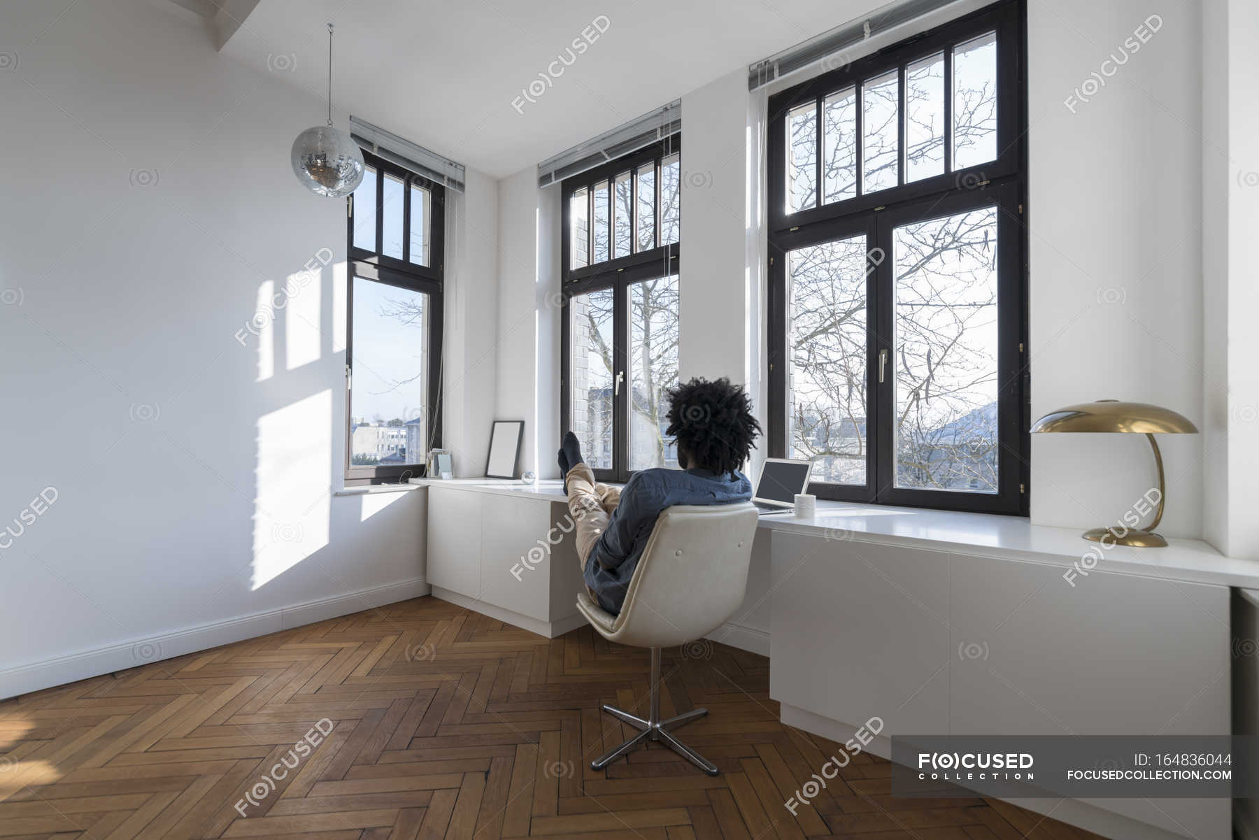 Man Sitting In Minimalist Empty Room Stock Photo