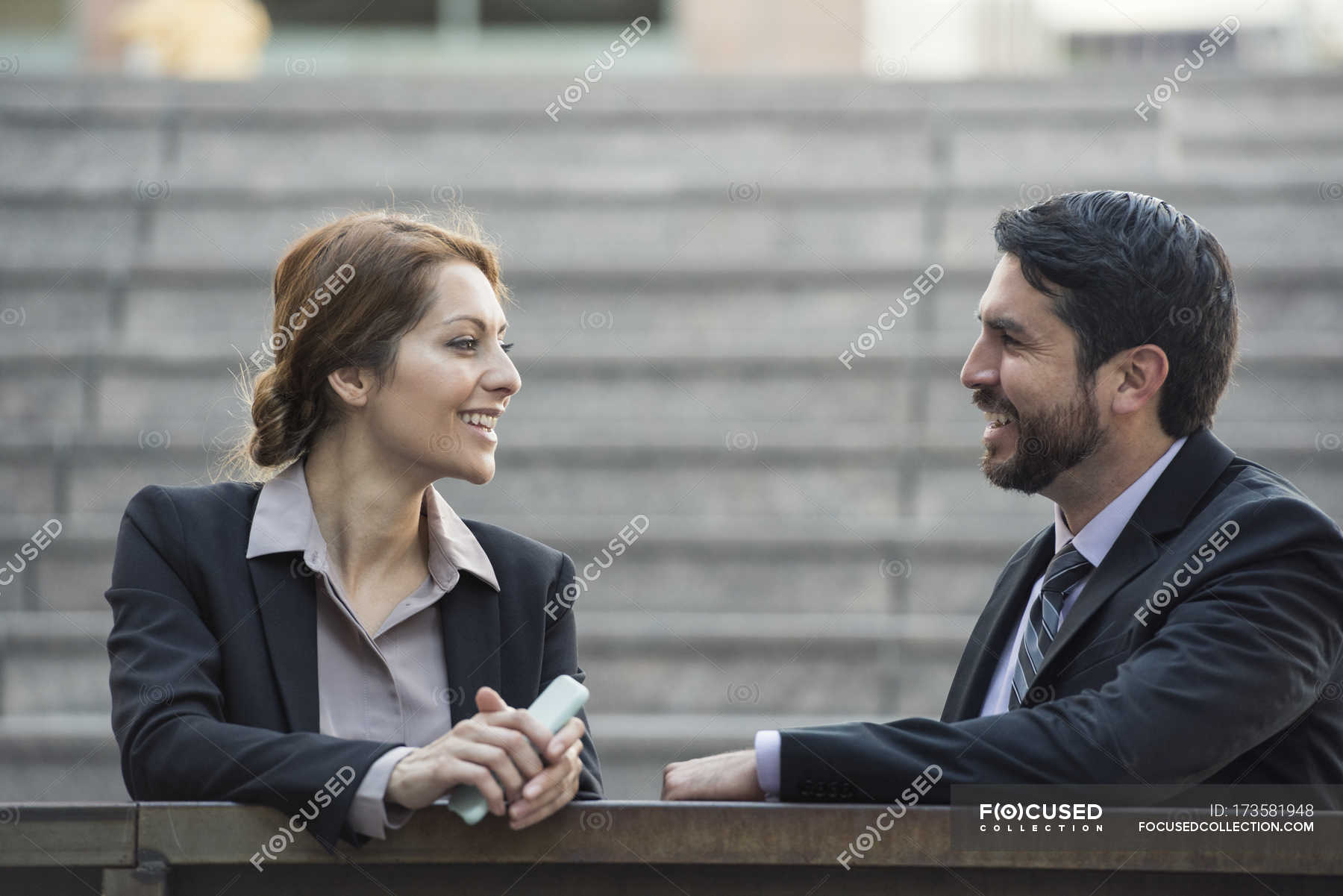 focused_173581948-Smiling-businesswoman-businessman-talking-outdoors.jpg