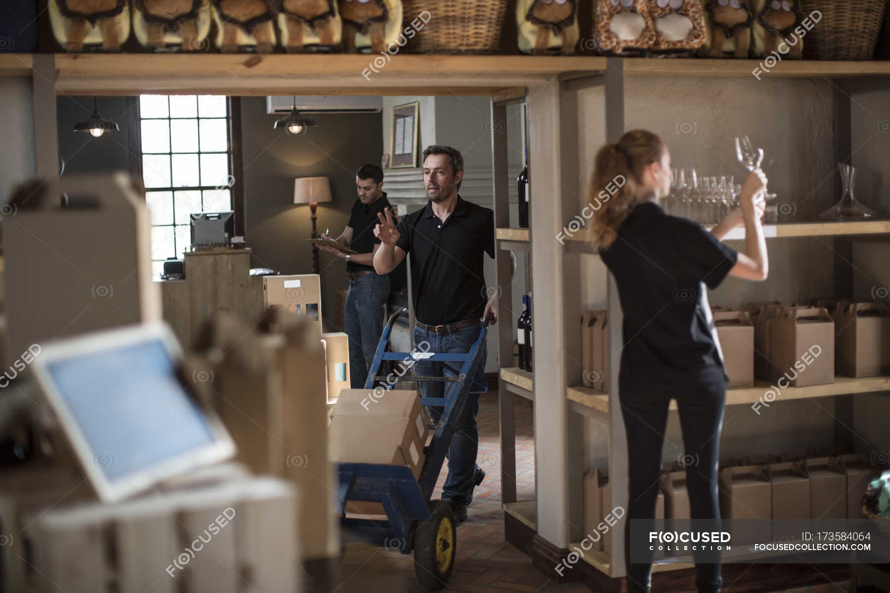Salesman On Floor Preparing Wine Shop Before Opening Selective