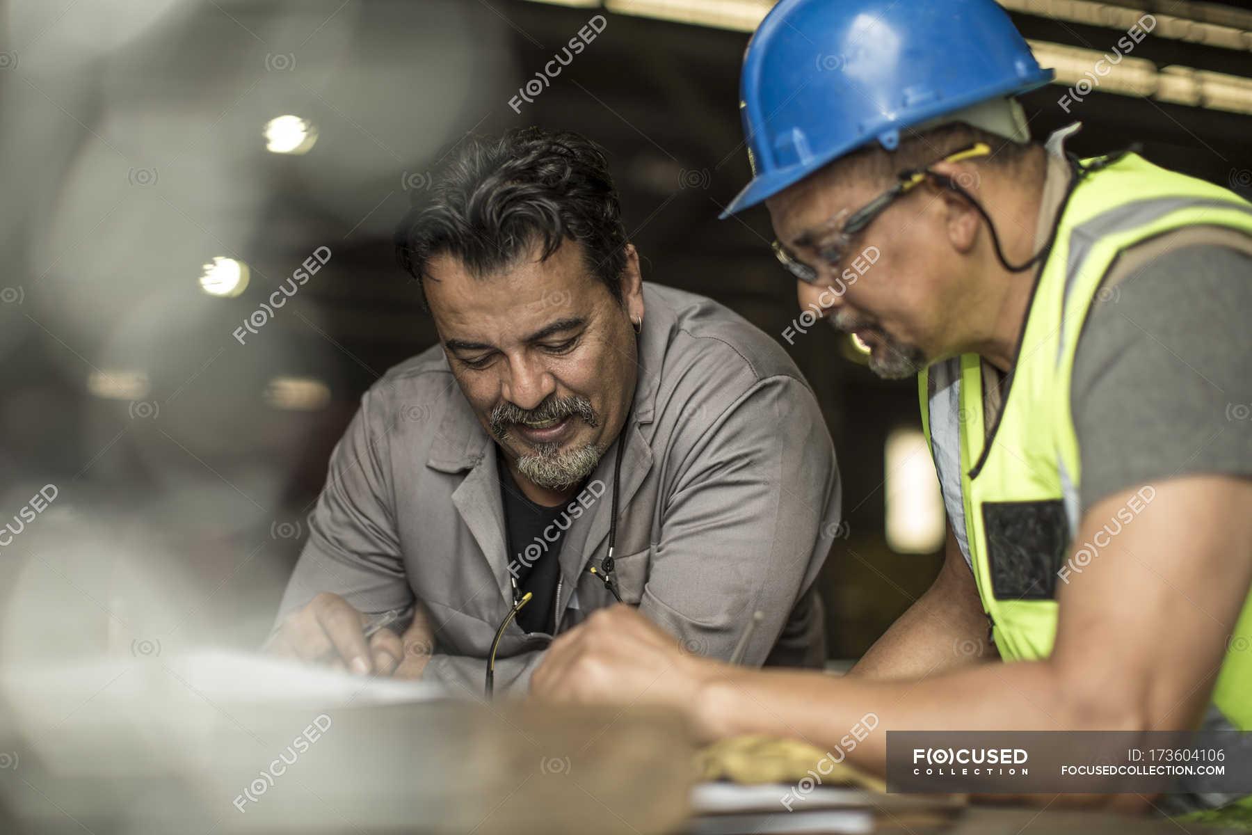 Assistenti tecnici che discutono di piani di costruzione for Foto di piani di costruzione di fattoria