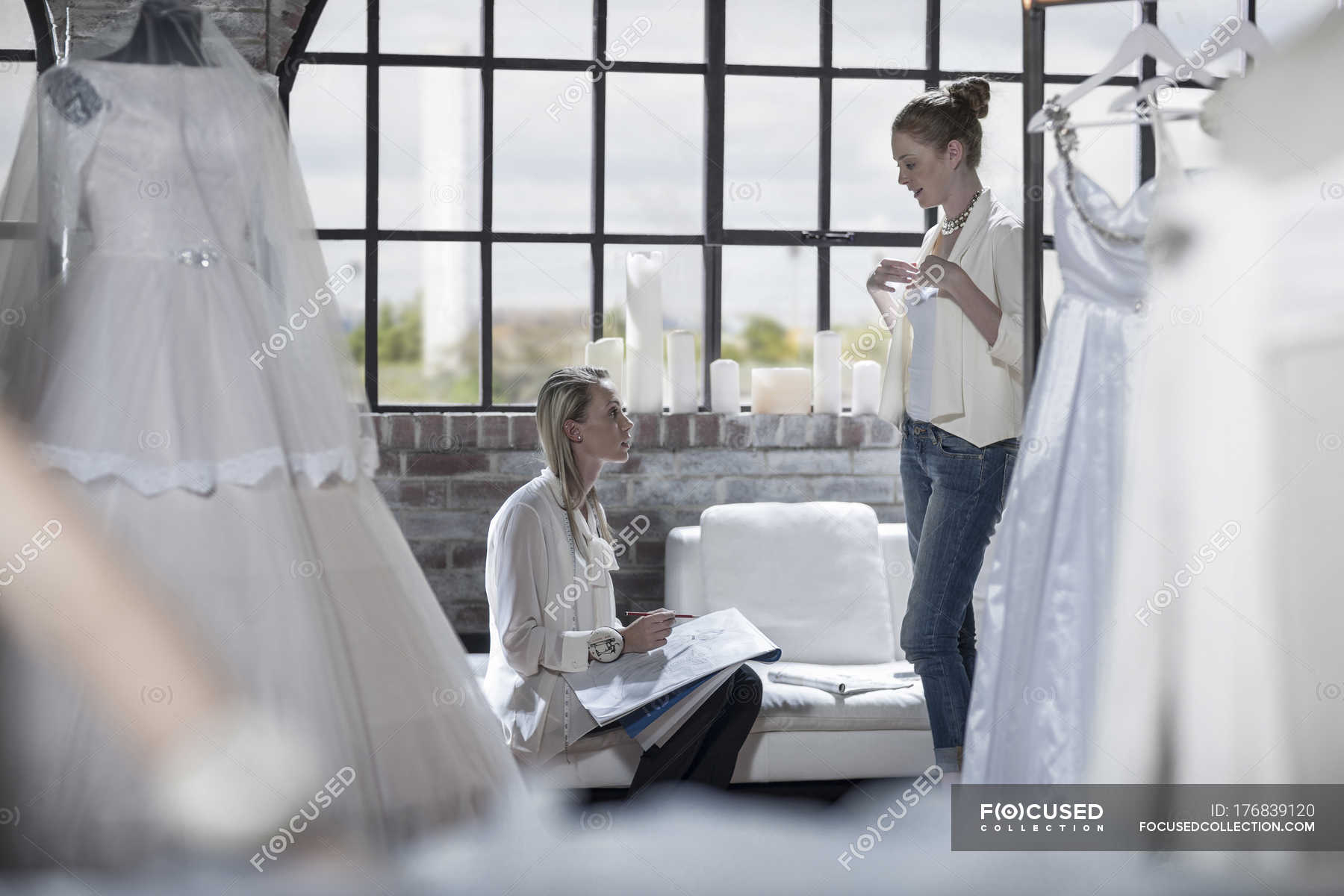 Designer And Bride To Be Discussing Wedding Dress In Fashion Studio Daytime Confidence Stock Photo 176839120