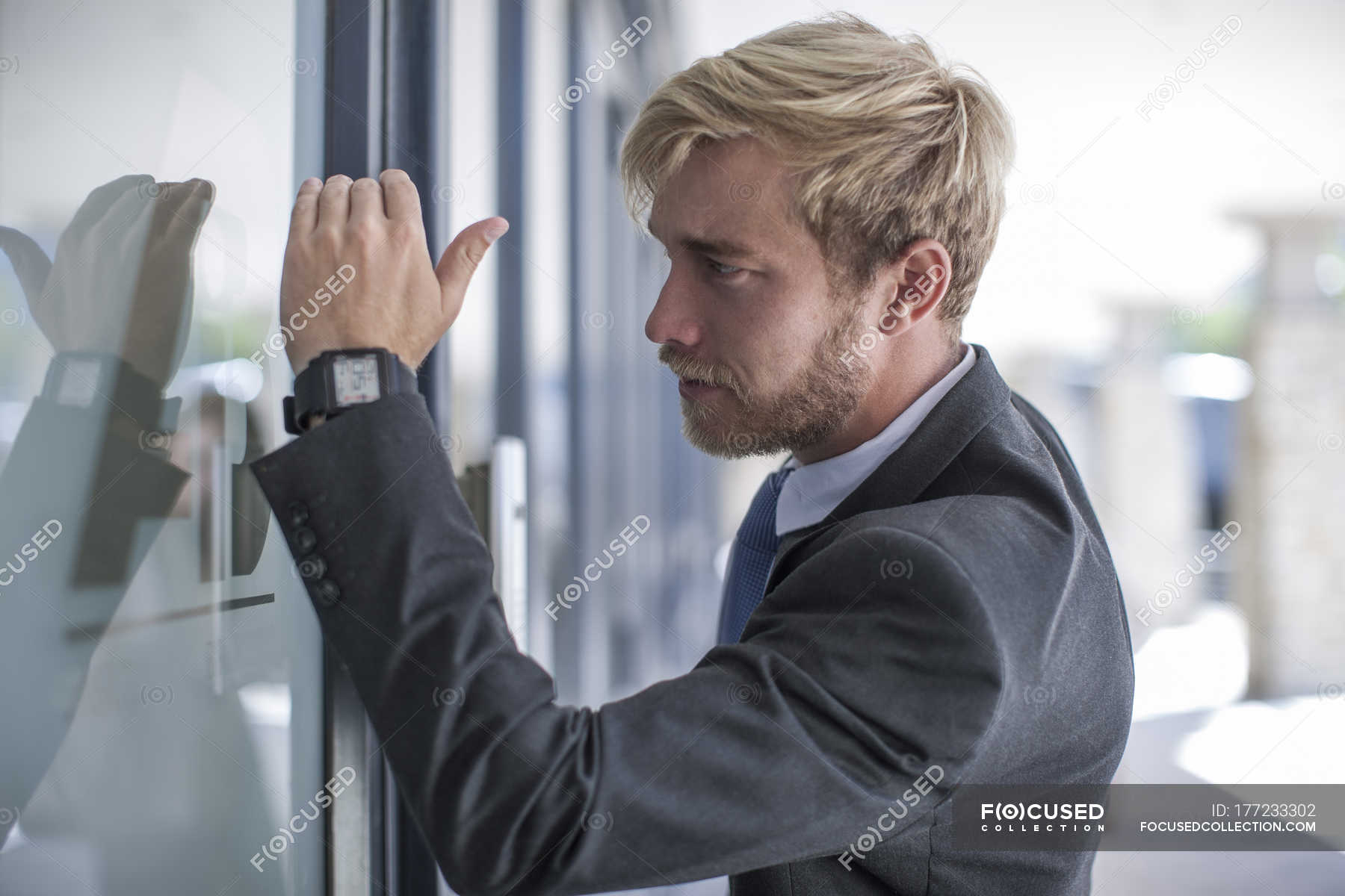 Businessman Looking Through Glass Door Stock Photo 177233302