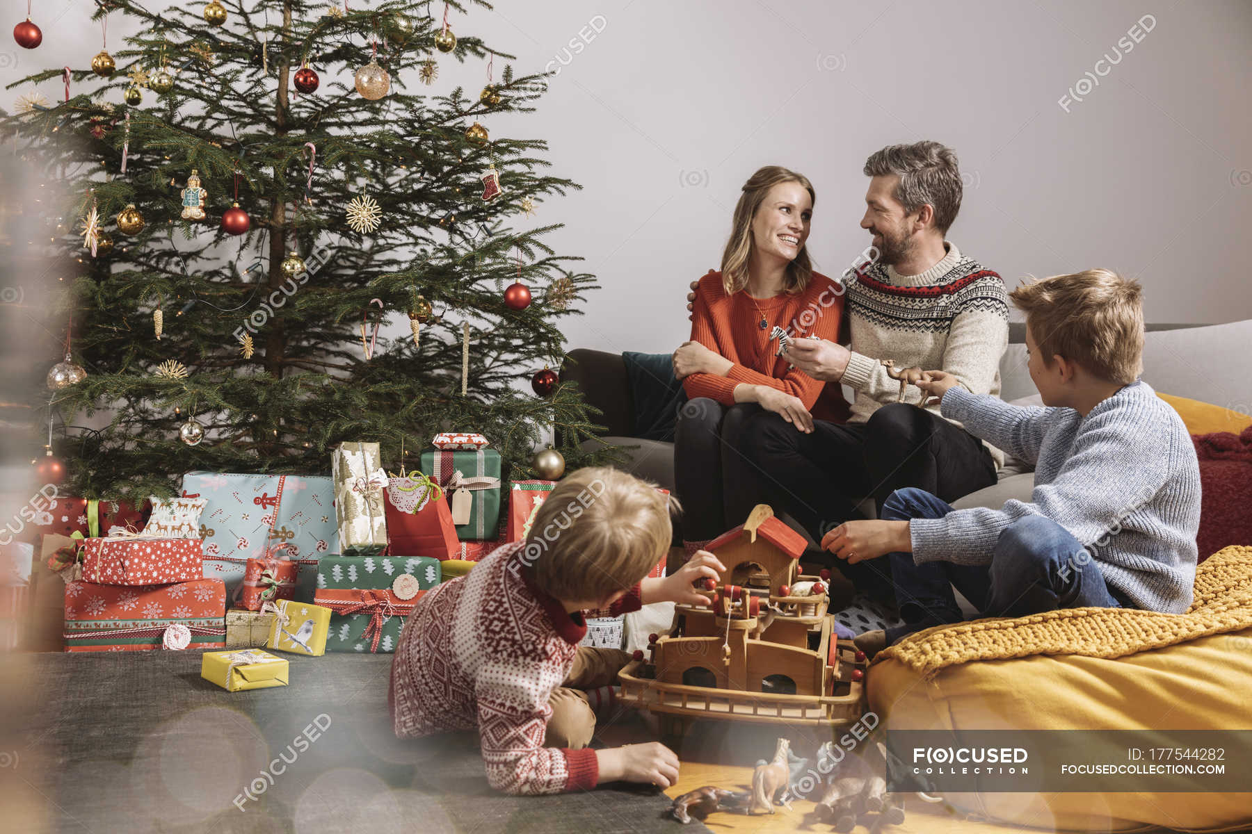 Family unwrapping Christmas gifts and playing with toys — christmas ...